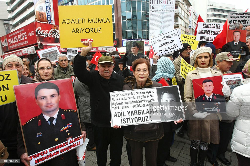 A group of protesters including the family members of more than 300 jailed military officers accused of plotting to overthrow Turkey's Islamic-rooted government, hold banners as they stage a demonstration for 'justice and fair trial' in Ankara on February 16, 2013. In September 2012 more than 300 retired and active military officers received prison sentences of up to 20 years after the court ruled that a military exercise dubbed 'Sledgehammer' in 2003 was an undercover coup plot. Pro-government circles have praised the investigations as a step toward democracy but critics have branded them witch-hunts aimed at stifling opposition. AFP PHOTO/ADEM ALTAN