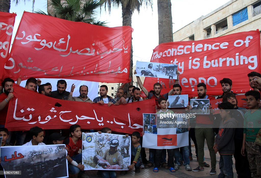 A group of protestors hold banners and pictures of victims to protest air strikes conducted by the Assad regime and Russia over the Aleppo in Idlib, Syria on May 4, 2016.