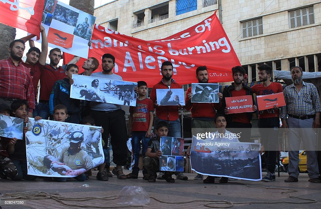 A group of protestors hold banners to protest air strikes conducted by the Assad regime and Russia over the Aleppo in Idlib, Syria on May 4, 2016.