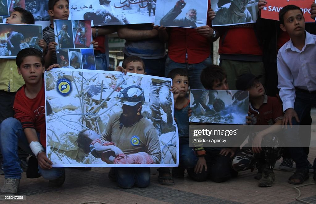 A group of protestors hold pictures of victims to protest air strikes conducted by the Assad regime and Russia over the Aleppo in Idlib, Syria on May 4, 2016.