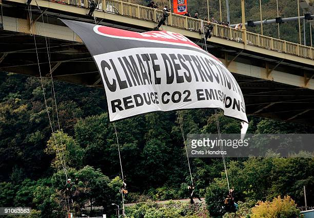 A group of protestors rappel from the West End Bridge with a banner denouncing climate change near downtown ahead of the G20 summit on September 23...