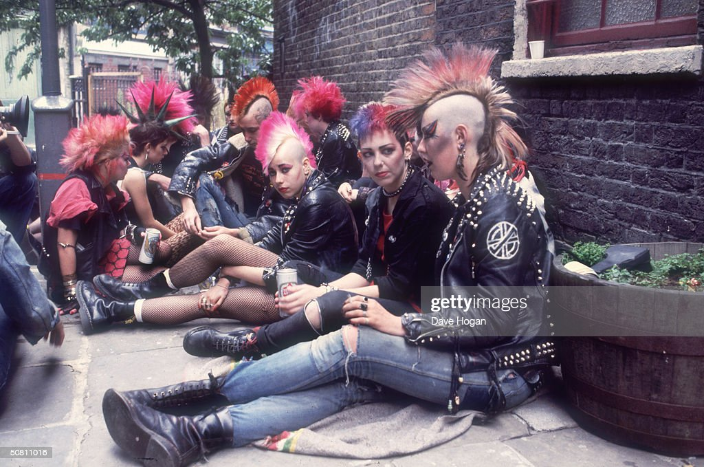 A group of punks colonise a street corner with a can of beer, 1983.