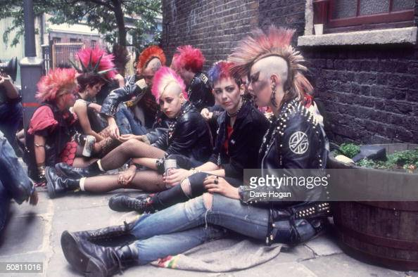A group of punks colonise a street corner with a can of beer 1983