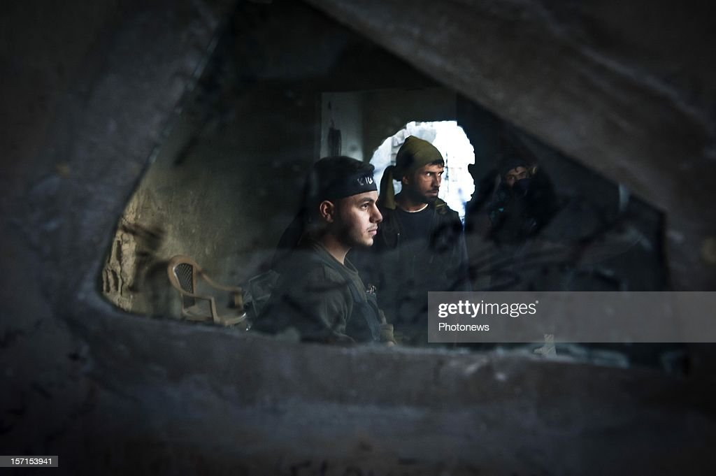 A group of rebels in a lookout on November 3, 2012 in Aleppo, Syria. The Shohada al Haq, or 'Martyrs of Truth' brigade control an area on the edge of the Salahudeen district in Aleppo, Syria's largest city. The brigade is made up of around 70 men, holding a handful of positions hidden in apartment blocks on the front line of Aleppo, facing toward Syrian army positions sometimes less than one hundred meters away. The Shohada al Haq use snipers to target Syrian regime troops as they move on the other side of the front, as well as moving between apartment blocks in the 'no man's land' between the two forces, occupying positions of advantage over the Syrian military. The brigade, or 'Katiba', live in the apartments they occupy, and the unit of rebel fighters is made up of former soldiers who defected from the Syrian military alongside men from Aleppo and other cities across Syria who have chosen to fight in Syria's increasingly violent civil war.