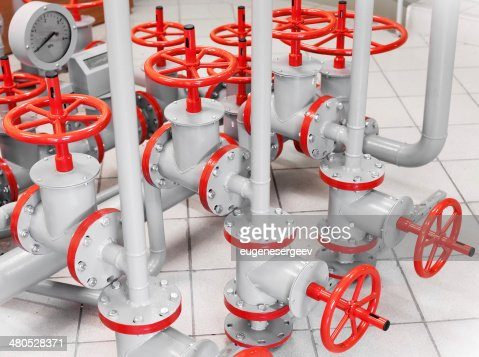 Group of red industrial valves on gray pipelines : Stockfoto