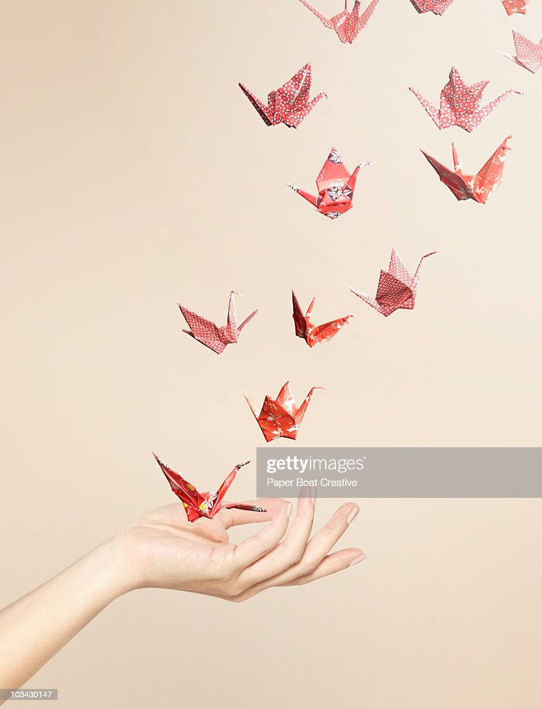 Group of red origami cranes flying away from hand : Stock Photo