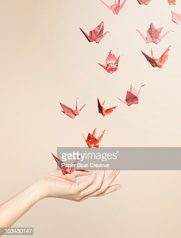 Group of red origami cranes flying away from hand