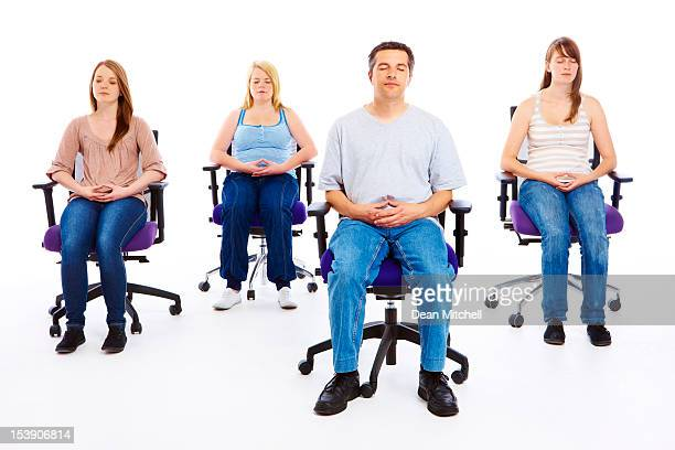 group of relaxed people meditating in seated position