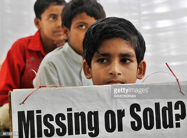 A group of rescued bonded Indian child labourers aged between seven and fourteen years old hold placards while taking part in a demonstration in New...