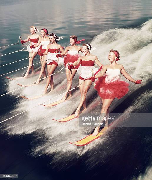 Group of retro young women waterskiing