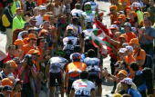 A group of riders passes through the 'orange tide' of Basque supporters during stage 12 of the Tour de France on July 16 2004 from Castelsarrasin to...
