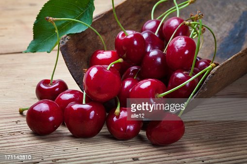 A group of ripe cherries on a wooden table