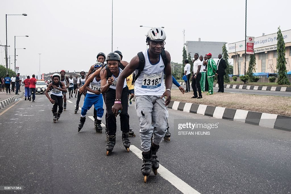 A group of rollerbladers participate in the Access Bank Lagos City Marathon on February 6, 2016. The Lagos City Marathon is one of the biggest races in Nigeria in over 30 years and attracted elite African long distance athletes and over 20,000 participants. / AFP / STEFAN HEUNIS