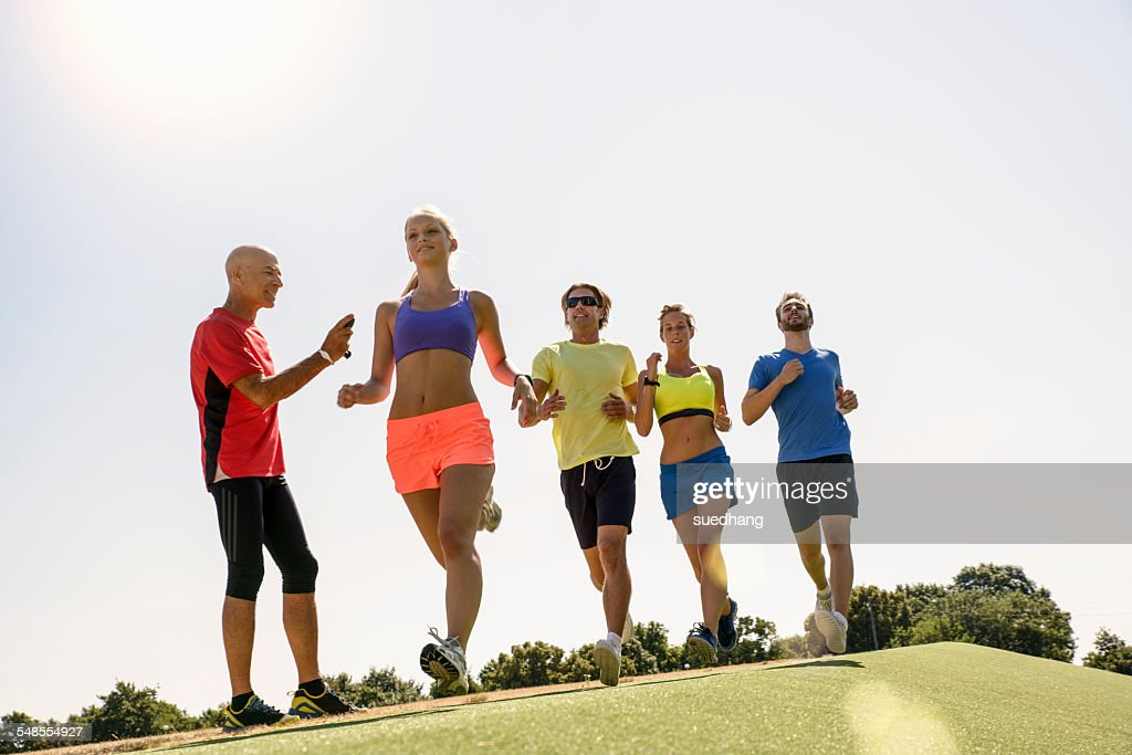 Group of runners being timed by trainer