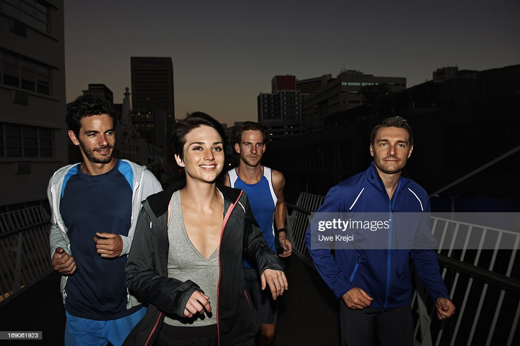 Group of runners in urban environment, at night : Stock Photo