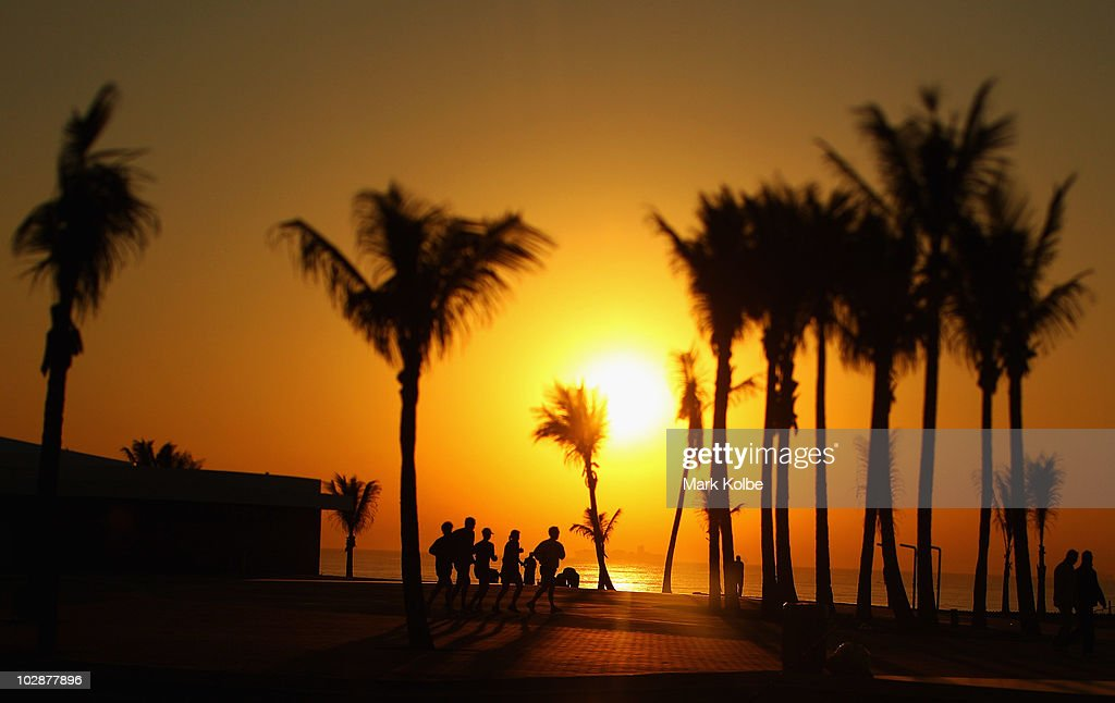 A group of runners jog along the foreshore as the sun rises over the Indian Ocean on June 19, 2010 in Durban, South Africa.