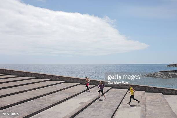 Group of runners on large stairs near ocean