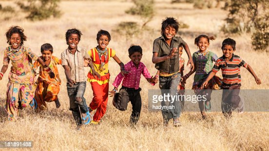 Group of running happy Indian children, desert village, India
