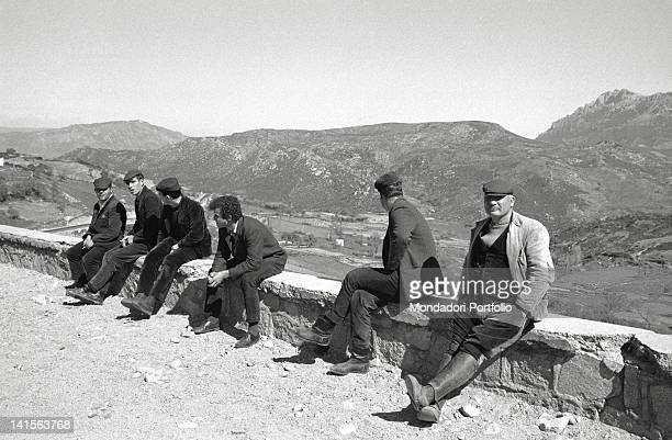 A group of Sardinian men sat down on a low wall under the sun Behind them the Barbagia valley in the province of Nuoro between Oliena and Orgosolo...