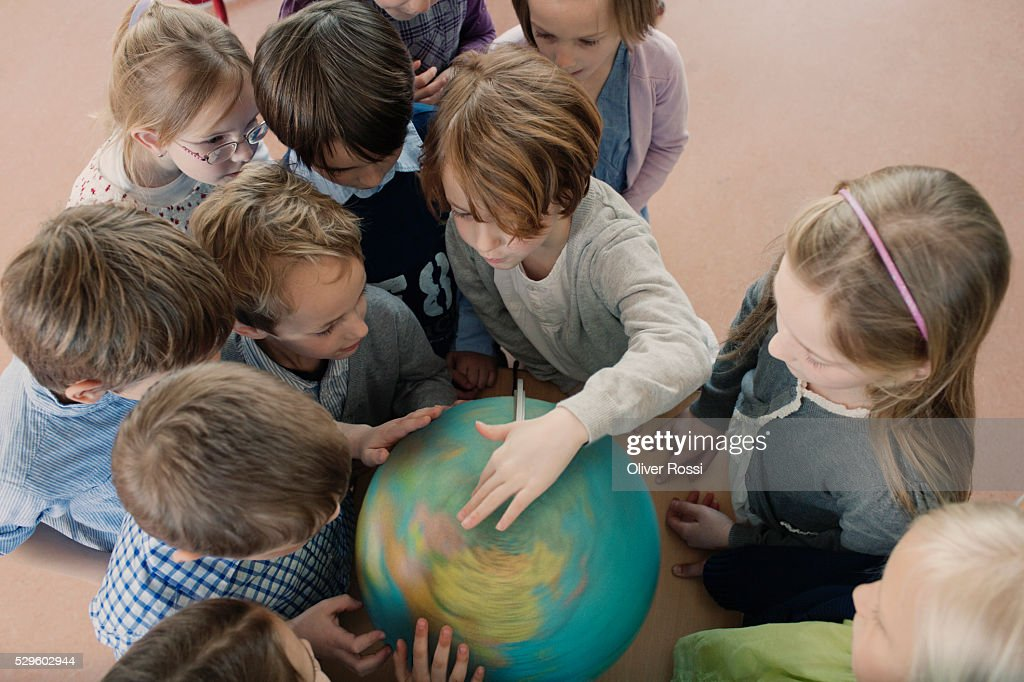 Group of school children (6-7) looking at globe : Stock-Foto