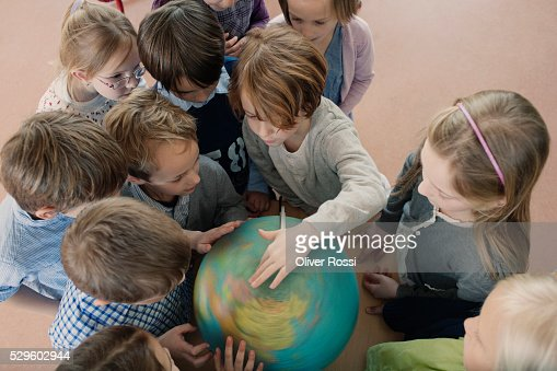 Group of school children (6-7) looking at globe : Foto de stock