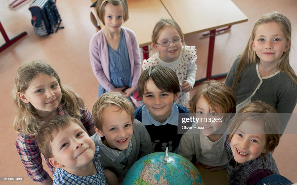 Group of school children (6-7) standing next to globe : Stockfoto