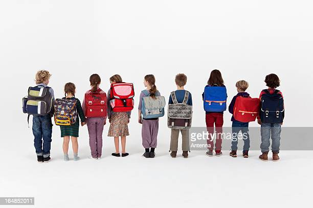 A group of school children wearing backpacks and standing in a row, rear view