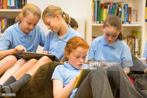 Group of school girls using tablet computers in the library