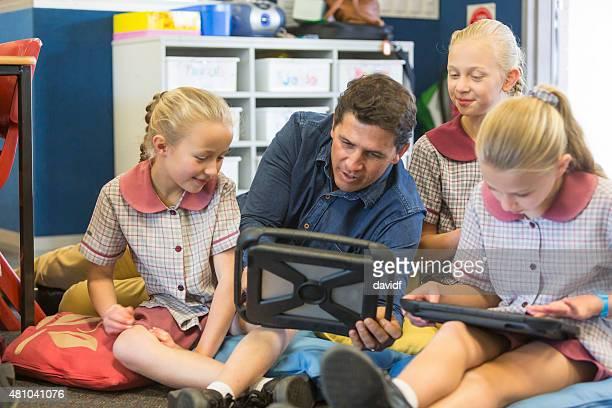 Gruppe von Schulmädchen mit Tablet-Computer mit Lehrer