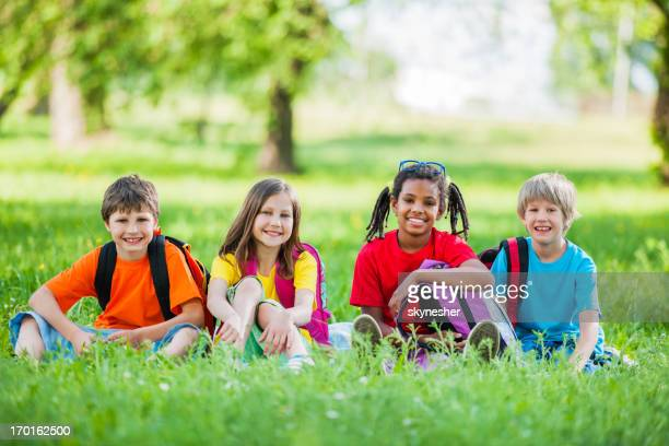 Group of school kids sitting in park.