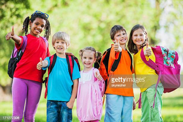 Group of school kids with their thumbs up.