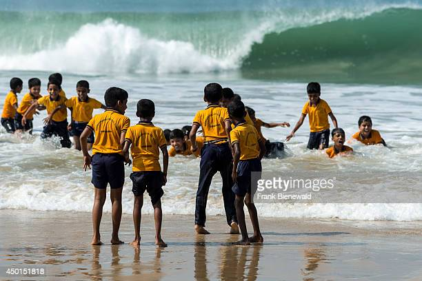 A group of schoolboys wearing yellow shirts are standing on the beach some are playing in the waves