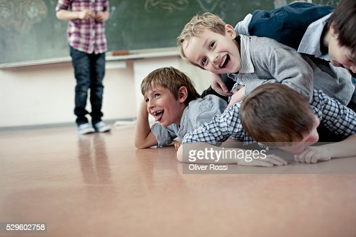 Group of schoolchildren (6-7) playing in classroom : Bildbanksbilder