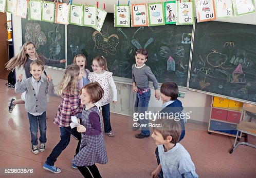 Group of schoolchildren (6-7) playing in classroom : Stockfoto