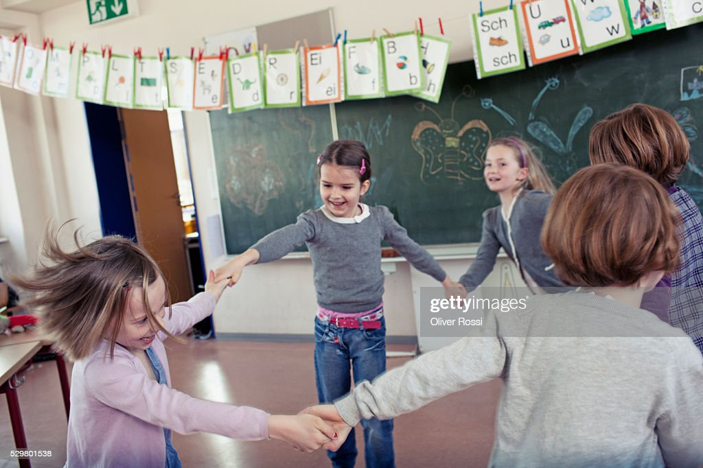 Group of schoolchildren (6-7) playing in classroom : Photo