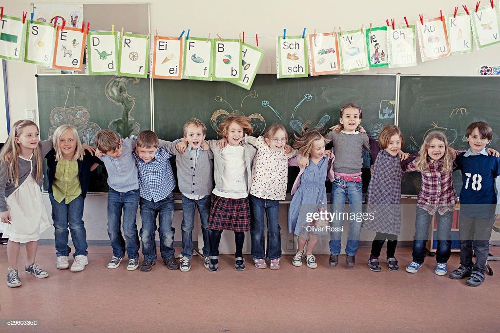 Group of schoolchildren (6-7) posing in front of blackboard : Stock-Foto