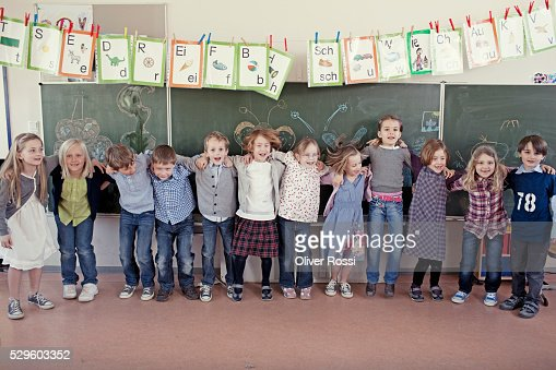 Group of schoolchildren (6-7) posing in front of blackboard : Photo