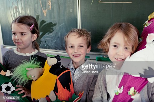 Group of schoolchildren (6-7) posing in front of blackboard with their toys : Foto de stock