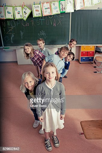 Group of schoolchildren (6-7, 8-9) posing together in classroom : Stock Photo