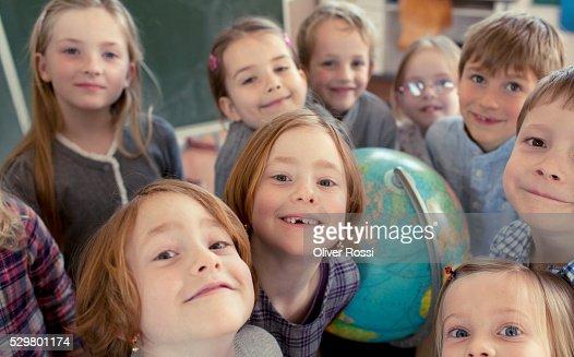 Group of schoolchildren (8-9) standing in classroom : Stock Photo