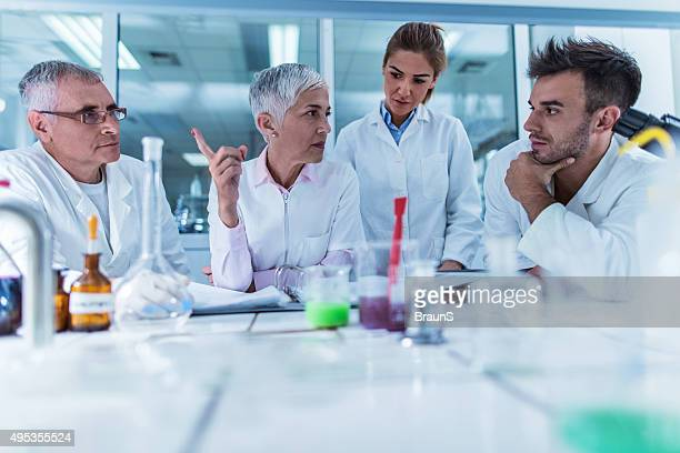 Group of scientist communicating on a meeting in laboratory.