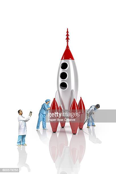group of scientists next to a cute rocket ship