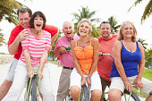 Group Of Happy Senior Friends Having Fun On Bicycle Ride Outdoors Smiling