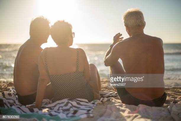 A group of senior friends relaxing at the beach in summer