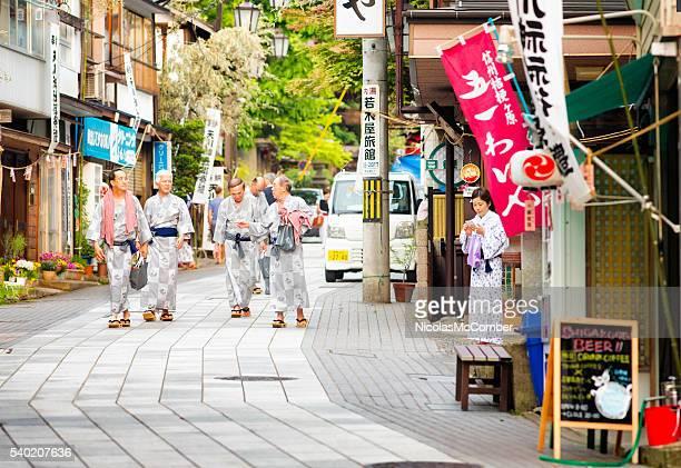 Group of senior Japanese men walking to Onsen wearing Yukatas