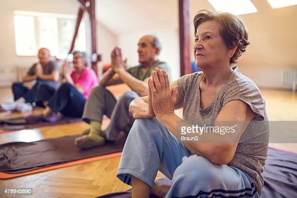 Group of senior men and women doing meditation exercises.