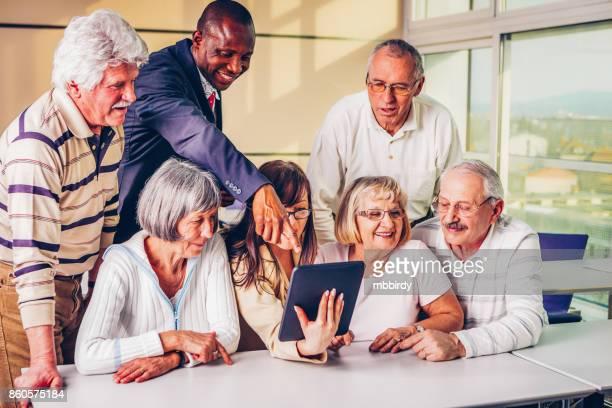 Groep senioren en jonge volwassenen kijken naar digitale tablet