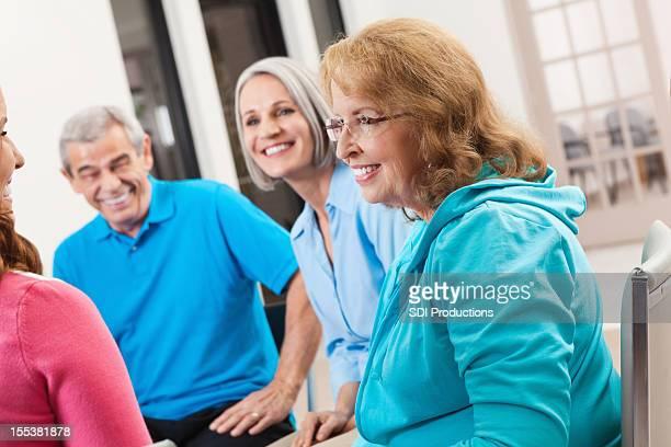 Gruppe von Senioren über etwas während Unterstützung meeting