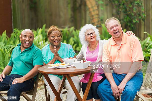 Group of seniors eating and laughing outdoors