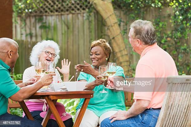 Group of seniors enjoying wine and food in back yard